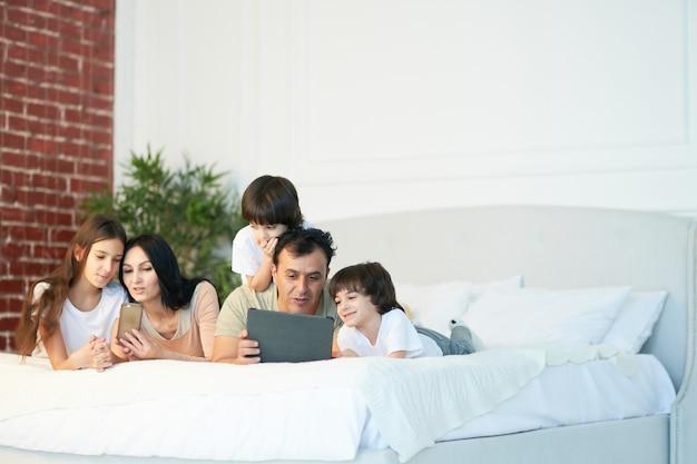 침대에 누워 디지털 장치를 사용하는 귀여운 어린 아이들과 함께 기술 행복한 라틴 가족