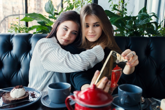 テクノロジー、ライフスタイル、食べ物、人、10代、コーヒーのコンセプト-市内中心部でスマートフォンを使って自分撮りをしている2人の若い女性。人々の幸せの概念、お茶を飲む