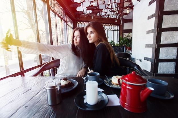 テクノロジー、ライフスタイル、食べ物、人、10代、コーヒーのコンセプト-市内中心部でスマートフォンを使って自分撮りをしている2人の若い女性。人とテクノロジーに関する幸福の概念