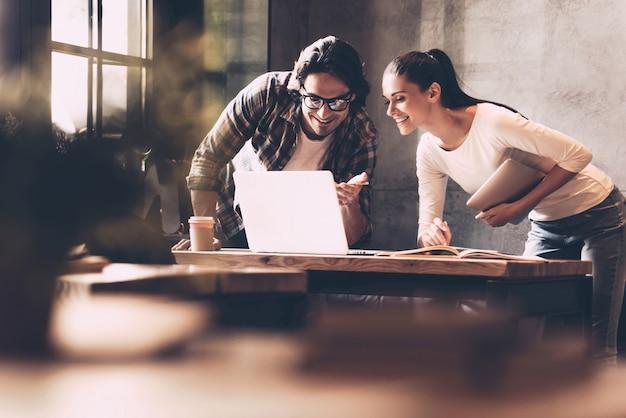 비즈니스를 더 쉽게 만드는 기술. 자신감 있는 젊은 남성과 여성이 노트북을 보고 웃고 있는 동안 둘 다 창의적인 사무실에서 책상 근처에 서 있습니다.