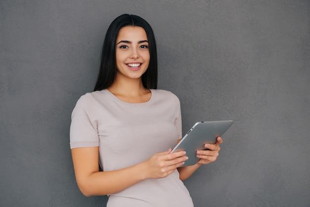 삶을 더 쉽게 만드는 기술. 디지털 태블릿을 들고 있는 아름다운 젊은 여성과