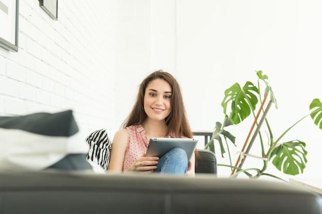 기술, 사람들 개념-젊은 여자가 소파에 앉아 태블릿을 보거나 서핑을