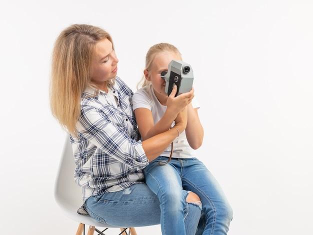 技術、写真撮影、家族のコンセプト-白い背景の上にレトロなカメラを使用して母と娘。
