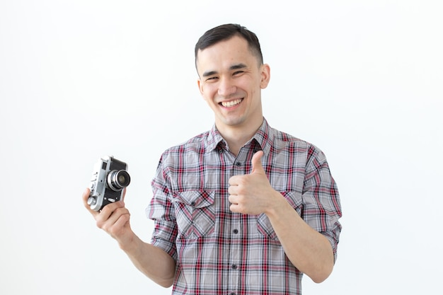 Technologies, photographing and people concept - handsome asian young man with retro camera