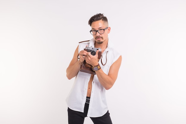 Technologies, photographing and people concept - handsome young man with retro camera over white background.