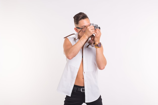 Technologies, photographing and people concept - handsome young man with retro camera over white surface