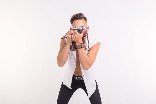 Technologies, photographing and people concept - handsome young man with retro camera over white surface.
