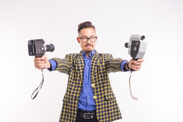 Technologies, photographing and people concept - handsome young man with two retro cameras smiling over white surface.