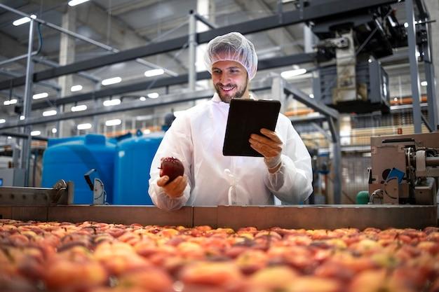 식품 가공 공장에서 사과 과일 생산의 품질 관리를하는 기술자.