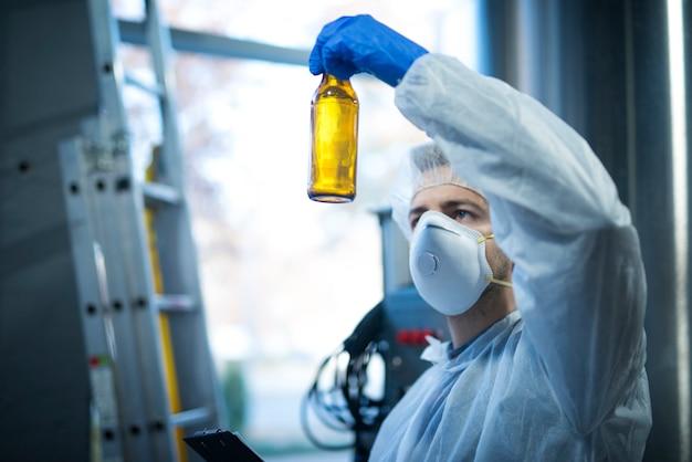Эксперт-технолог на заводе по производству пива держит стеклянную бутылку и проверяет качество