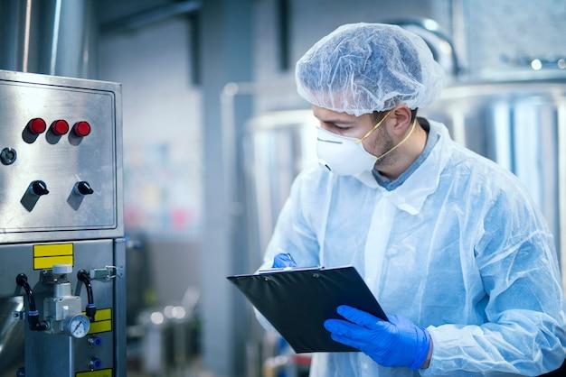 Эксперт-технолог в защитной униформе с сеткой для волос и маской, снимающей параметры с промышленного оборудования на предприятии по производству пищевых продуктов.