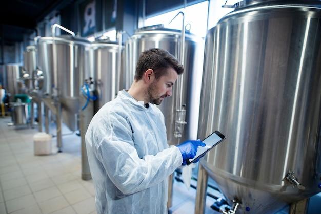 Эксперт-технолог стоит на заводе по производству продуктов питания и печатает на своем планшетном компьютере