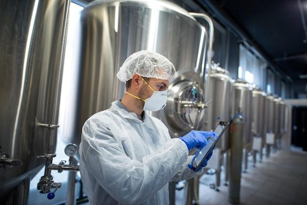 タブレットを保持し、工場工場での生産をチェックする防護服の技術者