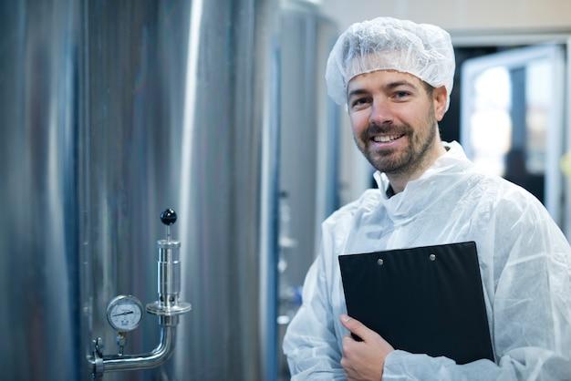 食品加工工場の圧力計付きクロームリザーバーのそばに立っている白い保護ユニフォームとヘアネットの技術者