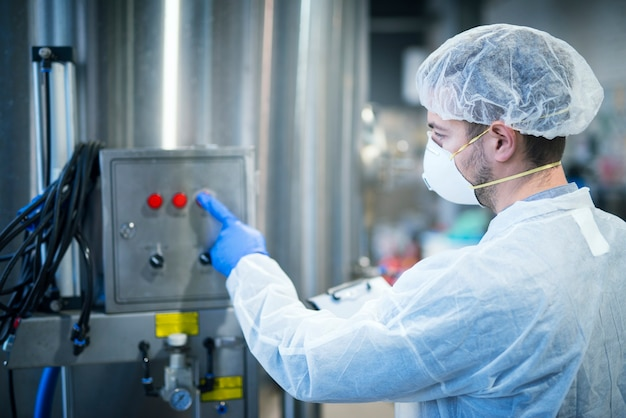 식품 가공을 위해 산업용 기계에서 작동하는 헤어 넷 및 마스크가있는 흰색 보호 유니폼을 입은 기술자