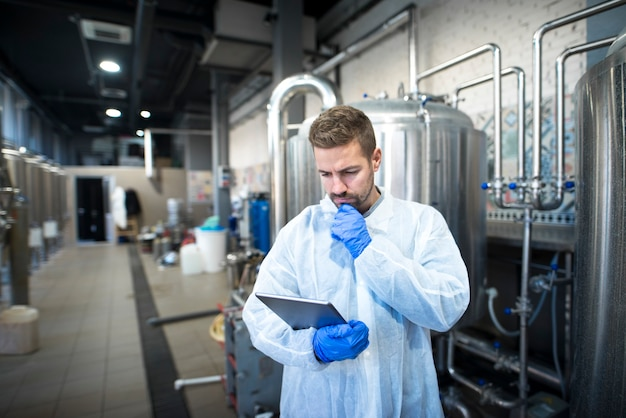 Technologist reading production reports on tablet computer in factory