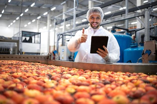 식품 가공 공장에서 엄지 손가락을 보이고 사과 과일의 품질을 확인하는 기술자.