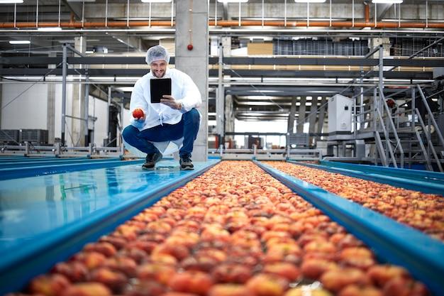 식품 가공 공장에 서서 사과 과일의 품질을 확인하는 기술자.