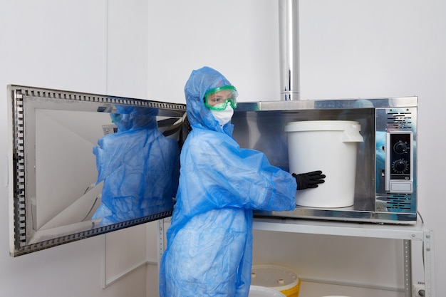 Технолог в перчатках с защитным костюмом ppe работает с большим пластиковым ведром в исследованиях