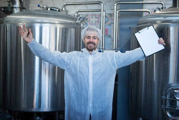 Technologist in white protective suit with raised hands celebrating success and good results in food factory