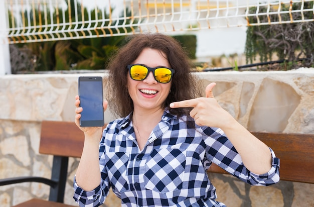テクノロジーと広告のコンセプト。空の画面でスマートフォンを示す美しい女性。