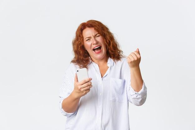 技術とコミュニケーションの概念。素晴らしいニュース、拳ポンプを喜んで喜んで幸せな中年赤毛の女性を獲得し、携帯電話を持っているように楽しく叫んでの肖像画