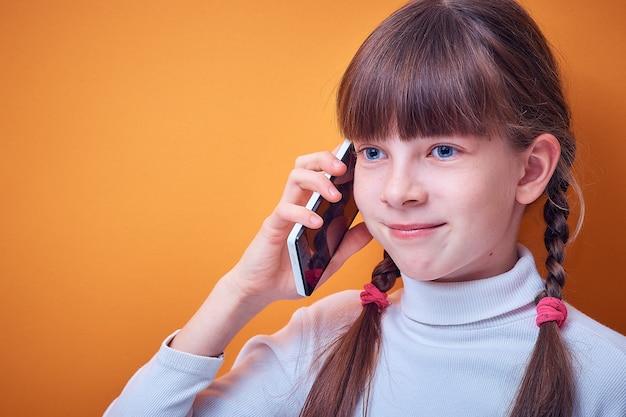 電話で話している技術とコミュニケーションの白人の十代の少女