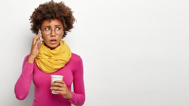 技術とコミュニケーションの概念。神経質な困惑した女性が携帯電話で電話をかけ、見た目を不快にさせた