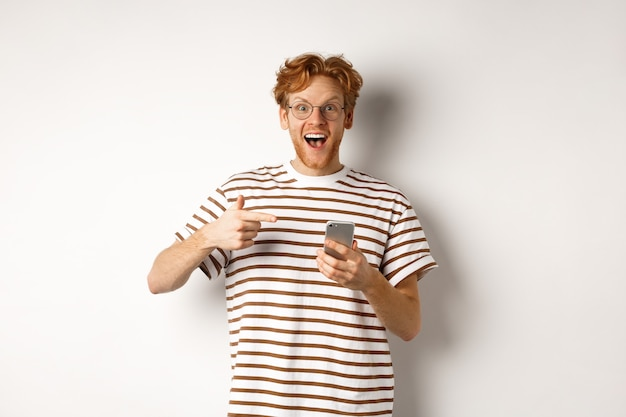 Концепция технологии и электронной коммерции. пораженный рыжий мужчина просматривает онлайн-промо-предложение на мобильном телефоне, указывая пальцем на смартфон и улыбается, белый фон