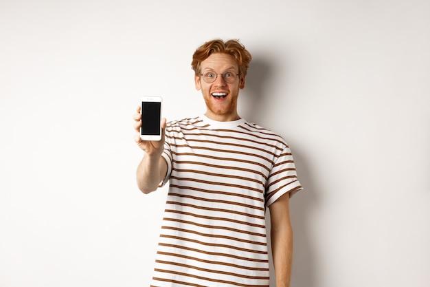 Концепция технологии и электронной коммерции. счастливый молодой рыжий человек в очках, показывая пустой экран смартфона, глядя на камеру изумлен, стоя на белом фоне.