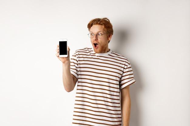 Концепция технологии и электронной коммерции. удивленный и шокированный рыжий парень просматривает онлайн-продвижение, показывая пустой экран смартфона и отвисшую челюсть, белый фон