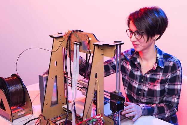 技術とエンジニアリングの概念-研究室で夜働いている女性エンジニア、彼は3dプリンターコンポーネントを調整しています