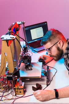 技術とエンジニアリングの概念-研究室で夜働いている男性エンジニアは、3dプリンターのコンポーネントを調整しています。
