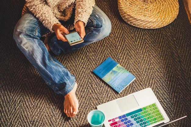 집에서 바닥에 휴대 전화 및 노트북을 사용하는 여자와 기술 및 현대 장치 전화 및 노트북 개념