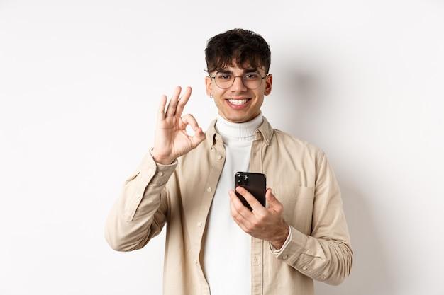 기술 및 온라인 쇼핑 개념. 스마트 폰을 사용하여 확인 제스처를 보여주는 안경에 잘 생긴 현대 남자의 초상화, 앱 또는 상점 추천, 흰 벽.