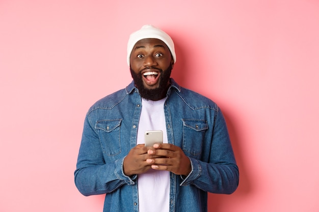 기술 및 온라인 쇼핑 개념입니다. 휴대폰을 사용하는 놀란 젊은 흑인 남성, 메시지를 읽은 후 카메라를 보고 놀라고 행복한 분홍색 배경
