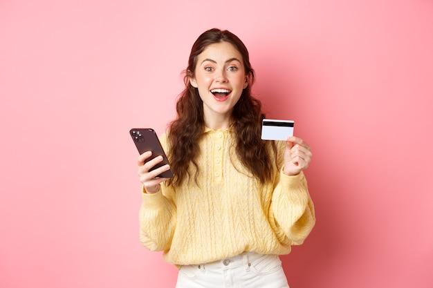 Технологии и покупки в интернете взволнованная девушка делает заказ, оплачивая онлайн с помощью пластиковой кредитной карты, держит мобильный телефон и улыбается в камеру розовая стена
