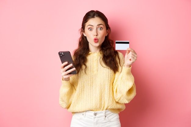テクノロジーとオンラインショッピング。プラスチックのクレジットカードを見せて携帯電話を持って、スマートフォンで支払い、オンラインで注文し、ピンクの壁に立って興奮している女の子の買い物客。