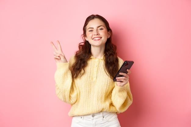 Технологии и интернет-магазины. счастливая молодая женщина, довольная улыбкой, держащая смартфон, показывающая v-знак и позитивный взгляд на камеру, стоящая над розовой стеной.