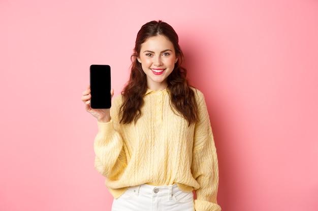 기술 및 온라인 쇼핑. 젊은 웃는 여자 결정, 다운로드 앱 광고, 화면에 스마트 폰 앱 표시, 분홍색 벽에 서서.