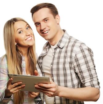 기술과 사람들의 개념 - 태블릿 pc 컴퓨터를 들고 있는 행복한 젊은 커플