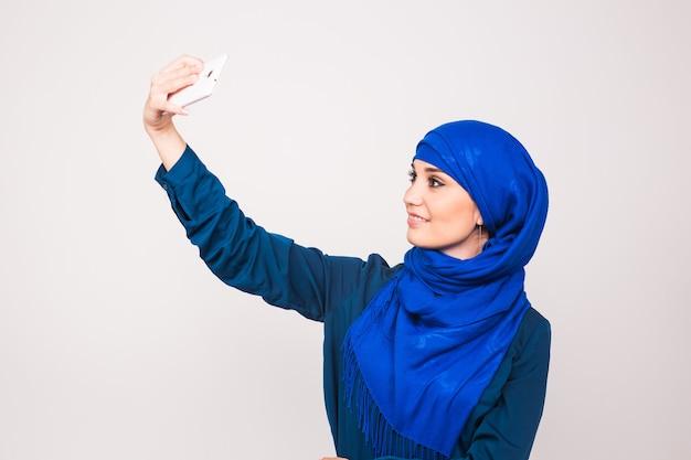 기술과 사람들 개념-흰색 배경 위에 스마트 폰에 hijab 복용 사진에 이슬람 여자.