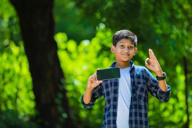 技術と人々の概念-空白の画面でスマートフォンを示す青いシャツの笑顔の10代の少年