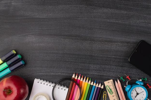 기술 및 학교 개념입니다. 스마트폰 사과와 카피스페이스가 있는 칠판에 격리된 다채로운 편지지의 오버헤드 뷰 사진 위