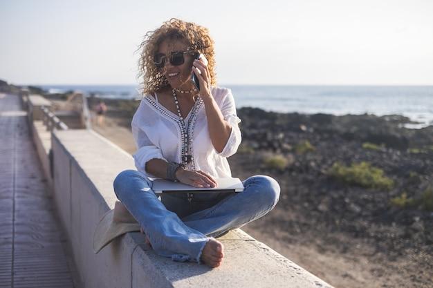 기술과 여행. 야외에서 일하기. 프리랜서 개념. 노트북 해변을 사용 하여 예쁜 젊은 여자.