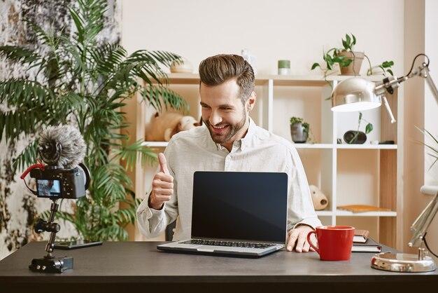 Блоггер технологий показывает на новый ноутбук, показывает палец вверх и улыбается во время потоковой передачи онлайн.