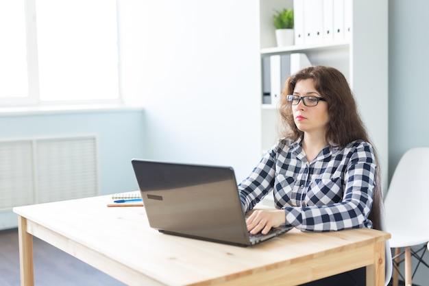 テクノロジー、ビジネス、人々の概念-オフィスのコンピューターで働く眼鏡をかけた真面目な女性。