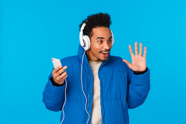 Technology, chatting concept. stylish attractive young african american male student in padded winter jacket, listening music on way university, hold smartphone headphones, waving hello, hi