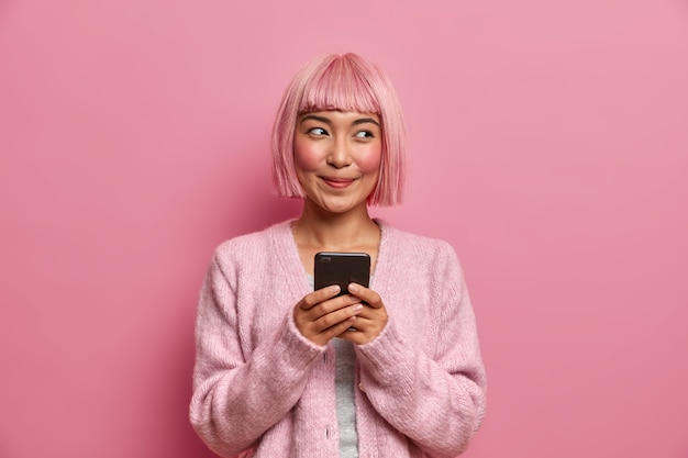 Концепция технологии, коммуникации и образа жизни. довольная мечтательная женщина с крашеными розовыми волосами, держит мобильный телефон, использует современное приложение для общения с друзьями,