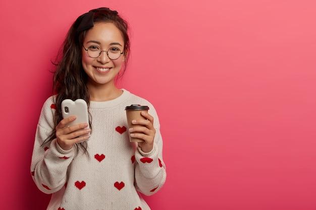 Концепция технологии, коммуникации и образа жизни. симпатичная молодая девушка в круглых очках использует смартфон для чтения классного блога и обмена сообщениями, пьет кофе на вынос, загружает приложение, стоит в помещении.